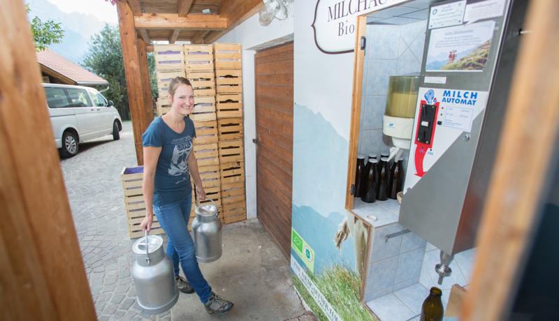 Hermine Baumgartner beim Bioheumilchautomaten beim Mesner Brennstadl in Gaimberg, den ihre Familie betreibt. Hier kann man rund um die Uhr Bioheumilch kaufen.